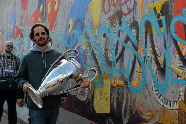 Max Herre carries the UEFA Champions League trophy along the Berlin Wall during the UEFA Champions League City Tour - Legendary Moments, Berlin