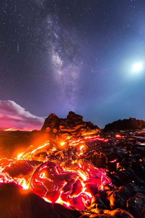 PIC BY MIKE MEZEUL II/CATERS NEWS - (PICTURED: Lava flows on the the Kilauea Volcano with the Milky Way a meteor and the moon above) - This photographer managed to score a real one shot wonder  by photographing lava, the Milky Way, the moon and a meteor all in the same photo. Mike Mezeul was in Volcanoes National Park on the Big Island of Hawaii when he seized the chance to capture the combination of natures beauty. The fiery red of the lava in the foreground is in deep contrast to the purple and blue hues of the galaxy beyond. In further photos lava is pictured pouring into the sea, creating billows of steam like natures very own foundry. SEE CATERS COPY.